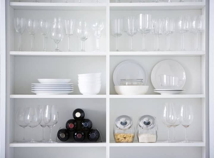 White kitchen cupboard filled with glassware and other items.